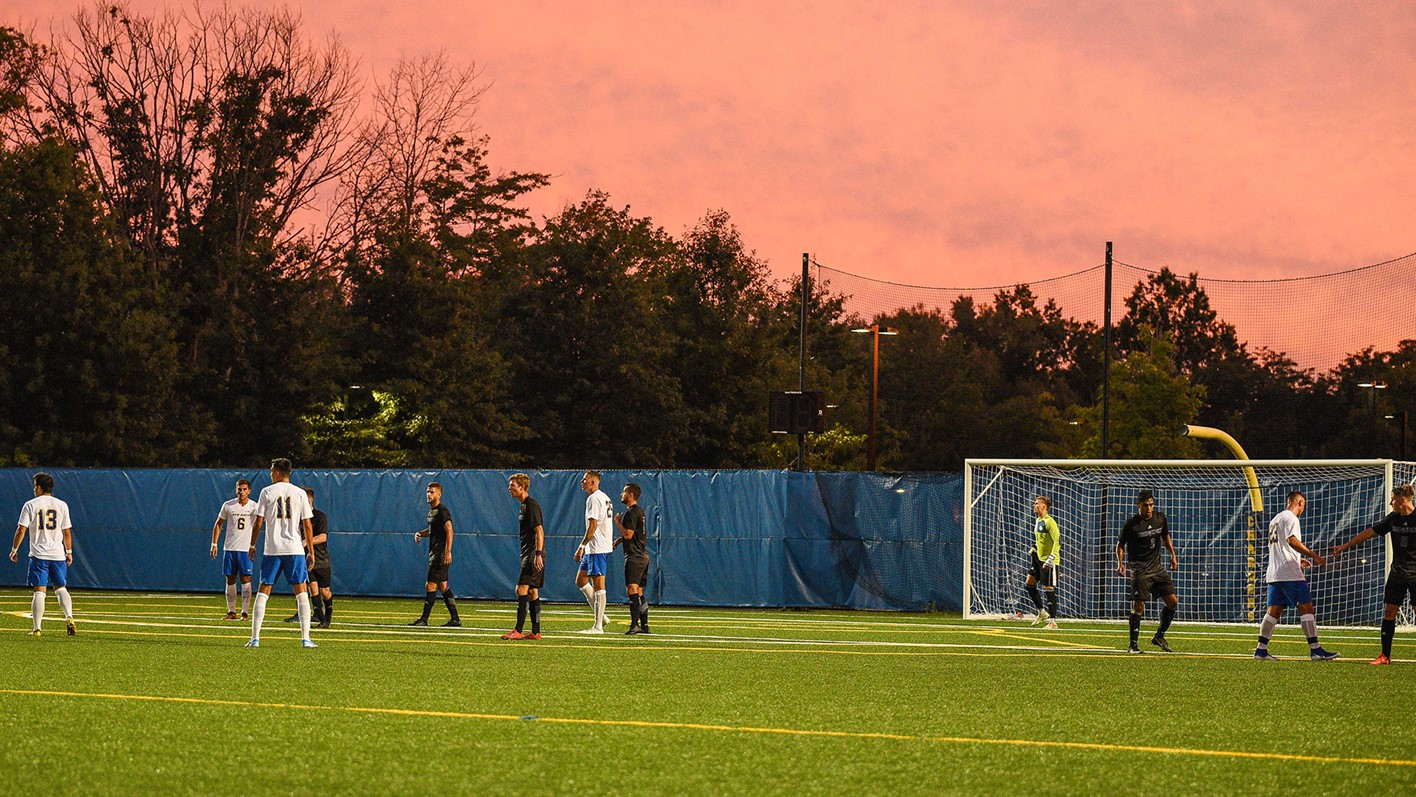 men's soccer match with a pink sunset