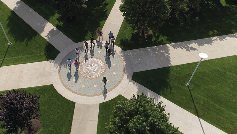 Photo of University of New Haven seal in the center of the Maxcy Quad.